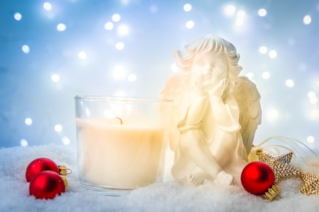 White Christmas  - burning advent candle and cute angel in snow , blue night with lights