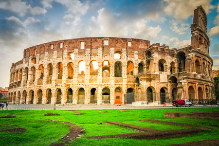 ruins of antique Colosseum with green grass lawn in sunise lights, Rome Italy, retro toned 스톡 콘텐츠