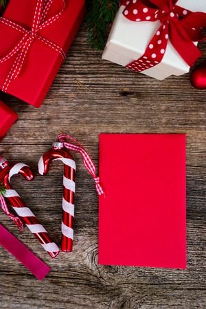 Christmas gift giving concept - christmas present boxes in red and white boxes on textured wooden table, copy space on red paper card