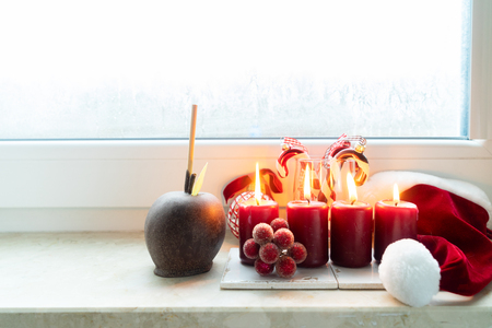 Christmas styled scene with red burning candles and chocolate glazed apple on windowsill Stock Photo