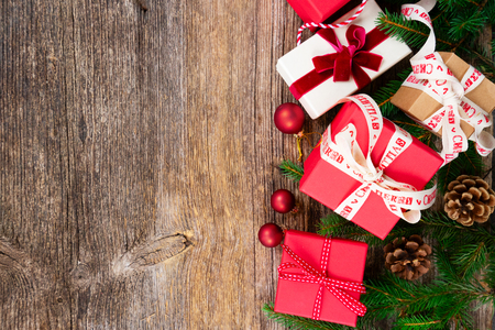 Christmas gift giving concept - christmas presents in red and white boxes on textured wooden table, top view row with copy space