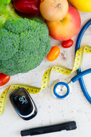 raw vegetables with blood glucose meter, lancet and stethoscope, diabetes healthy diet concept, top view
