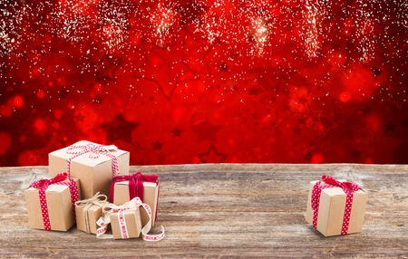 Handmade gift box on wooden table border over red festive background