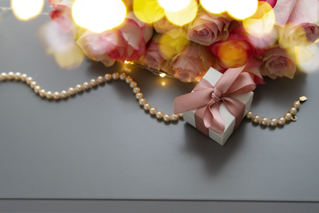 Rose fresh flowers bouquet with gift box on gray table from above, flat lay scene with bokeh lights Archivio Fotografico