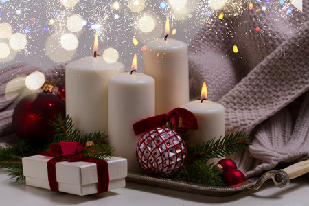 White burning advent candles with christmas decorationswith bokeh lights