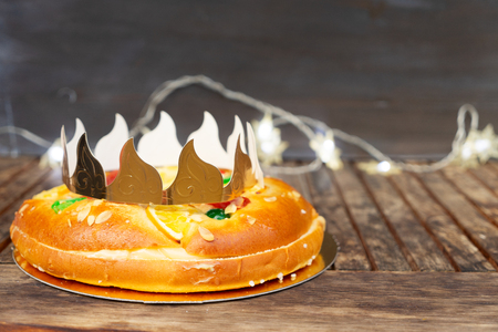 Roscon de Reyes traditional Spanish cake with crown for Epiphany festival on wooden table