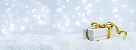 White christmas. gift box with golden ribbon bow in snow banner Stock Photo