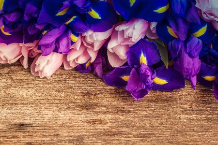 Bouquet of blue irises and pik tulips close up on wooden background, retro toned