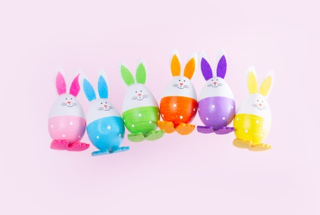 Row of falling funny easter bunnies on plain pink background