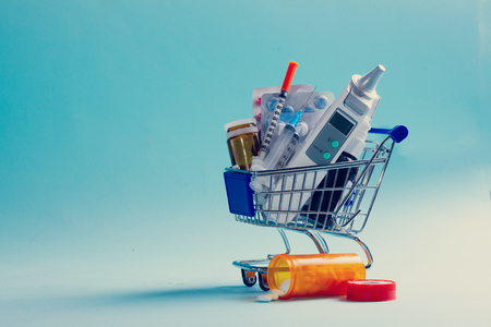 Healthcare concept - medical tools and medicaions in shopping cart on blue background, retro toned Banco de Imagens