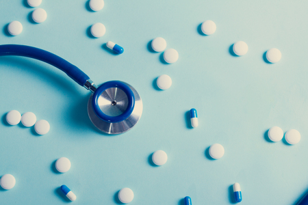 Healthcare concept - stethoscope and white pills on blue background, retro toned