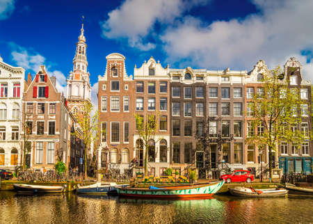 Facades row of old historic Houses over canal water with spring green trees, Amsterdam, Netherlands, retro toned