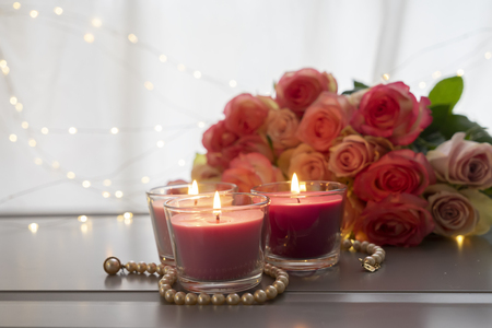 Glowing candles with rose fresh flowers bouquet on gray table, close up home interior details