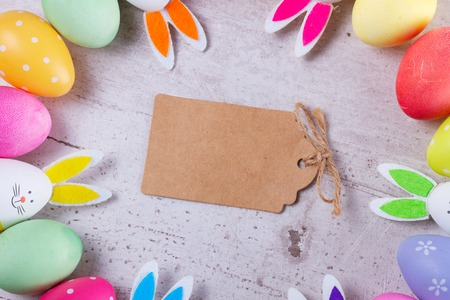 Easter scene with colored eggs and bunnies, top view, copy space on empty paper note Stockfoto