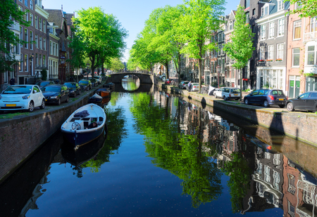 Bridge of Amsterdam over canal ring famous landmark in old European city, Amsterdam spring scenery with tree lush