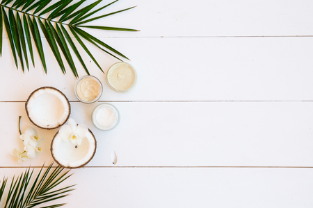 Coconut oil and cosmetics with palm leaves on white wooden background with copy space