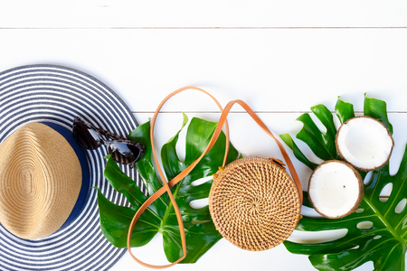 Summer flat lay scenery, bag, leaves and cocnut on white background with copy space Stock Photo