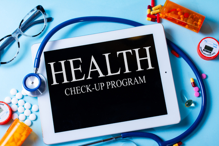 Pile of medical pills with blank tablet on blue background with health check-up program words