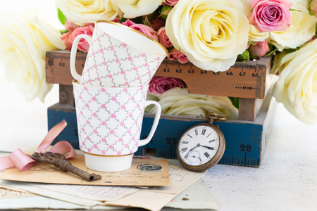 Pink and white roses flowers with two cofee cups and antique key