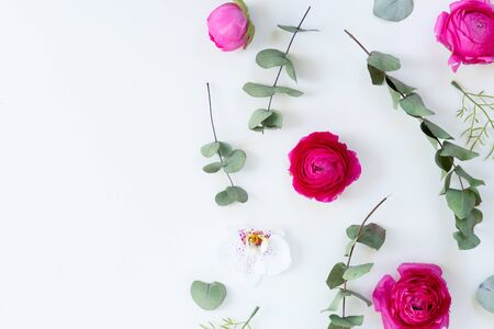Flowers composition. Border made of dried eucaliptus leaves and ranunculus flowers on white background. Flat lay, top view, copy space
