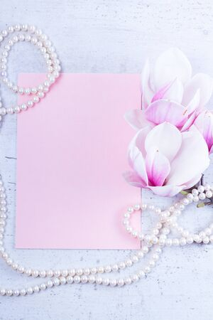 Magnolia flowers and pearl jewellery flat lay composition with copy space on pink paper background