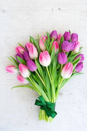 Bouquet of pink and violet tulip flowers on gray background, top view