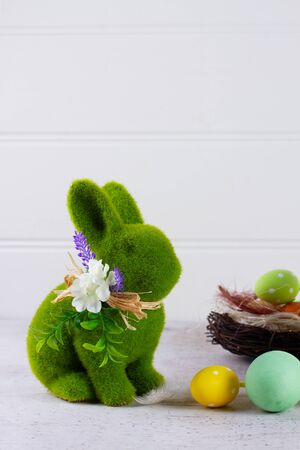Easter scene with colored eggs in nest and one green bunny over white