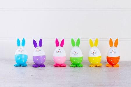 Row of funny easter bunnies of colored eggs over white