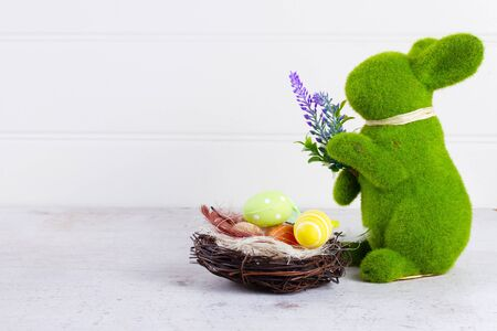 Easter scene with colored eggs in nest and one green bunny, copy spce over neutrl bckground