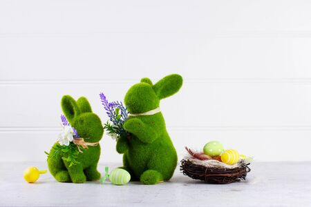 Easter scene with colored eggs in nest and two green bunnies over white Zdjęcie Seryjne