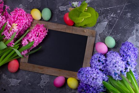 Easter frame with spring flowers, rabbit and colored eggs, low key, copy space on blackboard