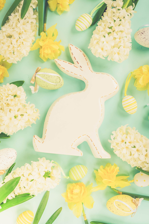 Easter frame with spring flowers, rabbit and colored eggs, flat lay on blue background, retro toned