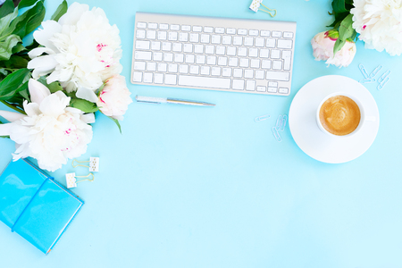 Flat lay top view home office workspace background with white modern keyboard, coffee and peony flowers, copy space on blue background