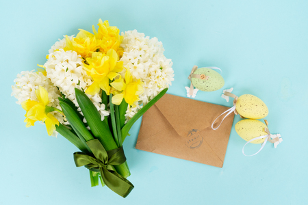 Easter bouquet with spring flowers, rabbit and colored eggs, flat lay on plain blue background