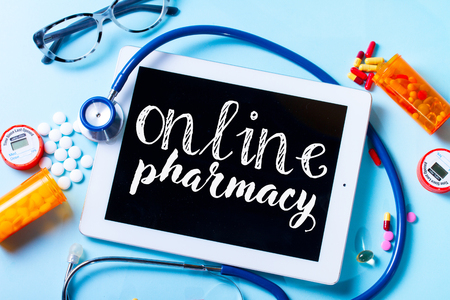 Online healthcare concept - medical pills and tablet on blue