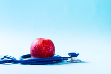 Healthcare concept - stethoscope and red apple on blue background with copy space