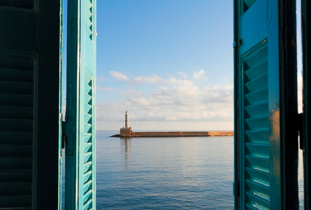 habour of Chania at sunny day, view through window blue sill, Crete, Greece