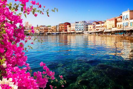 klares türkisfarbenes Wasser von Chania Hafen am sonnigen Tag mit Blumen, Kreta, Griechenland,