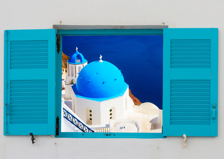Blick auf die klassische Kirche mit blauen Kuppeln durch das Fenster, Oia, Santorini, Griechenland Standard-Bild