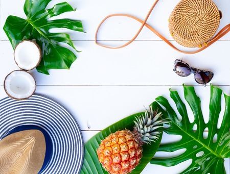 Summer flat lay frame with hat, bag, leaves and fruits on white background with copy space