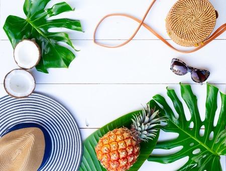 Cornice piatta estiva con cappello, borsa, foglie e frutti su sfondo bianco con spazio di copia