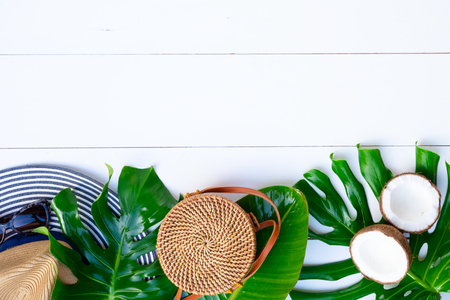 Summer flat lay scenery with hat, bag, leaves and cocnut on white background with copy space Stock Photo