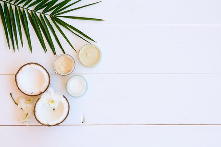 Coconut oil and cosmetics with palm leaves on white wooden background, top view with copy space