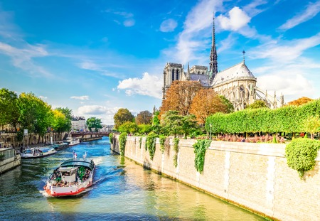 Notre Dame cathedral church over the Seine river with boat, Paris, France, retro toned