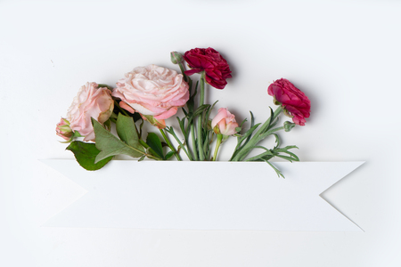Flowers layout with copy space for cards, wedding invitation, posters, save the date or greeting design. Layout made of ranunculus flowers on white background.