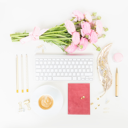 Flat lay top view home office workspace - modern keyboard with cup of coffee and pink ranunculus flowers