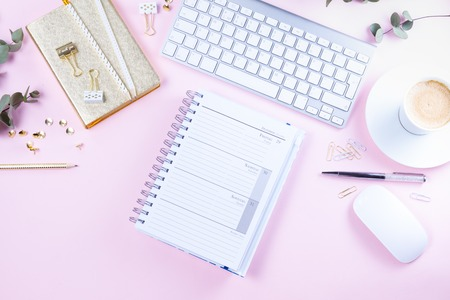 Flat lay top view home office workspace - white modern keyboard with notebook on pink desk background