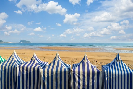 colorful blue and white tents of Zarauz beach, Pais Vasco, Spain