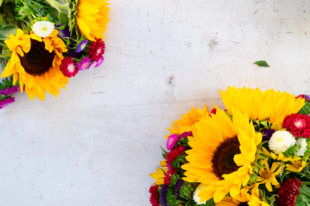 Sunflowers and aster fresh flowers, top view on white wooden table background with copy space