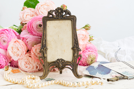 Pink fresh rose and ranunculus flowers, old mail and vintage frame with copy space